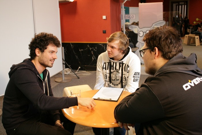 Nationalratsabgeordneter Julian Schmid diskutiert mit zwei Lehrlingen an einem kleinen Tisch
