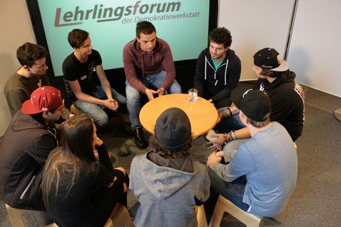 Nationalratsabgeordneter Julian Schmid diskutiert mit einigen Lehrlingen in einem kleinen Sesselkreis