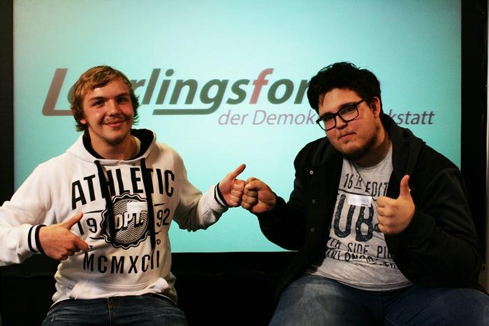 Zwei junge Männer deuten Daumen hoch