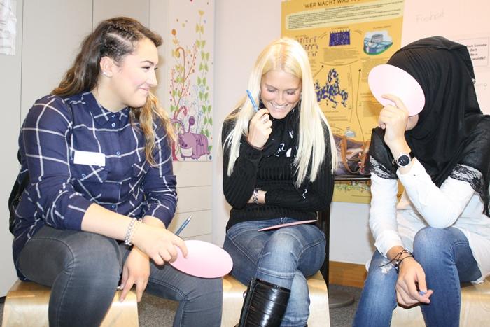 Drei junge Frauen lachen, eine verdeckt ihr Gesicht mit einem rosa Kärtchen