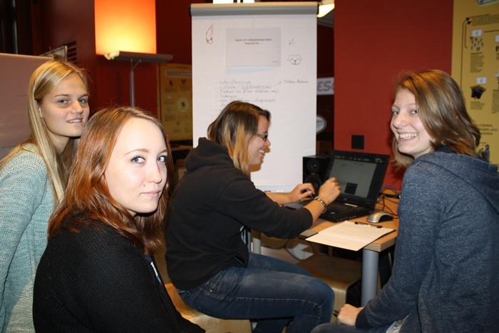 Vier junge Frauen arbeiten am Laptop an einem Artikel