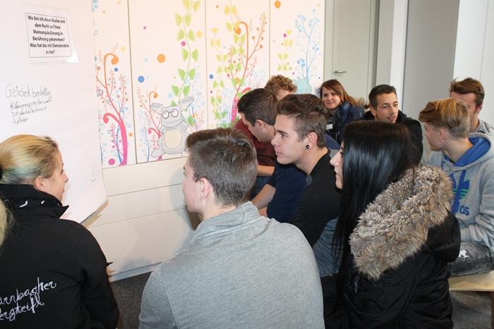 Lehrlinge sitzen in der Gruppe vor einem Flipchart