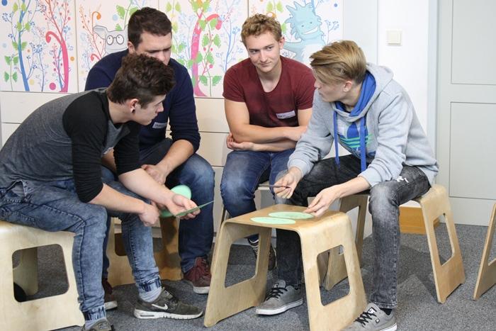 Vier junge Männer beschriften Kärtchen während einer Gruppenarbeit