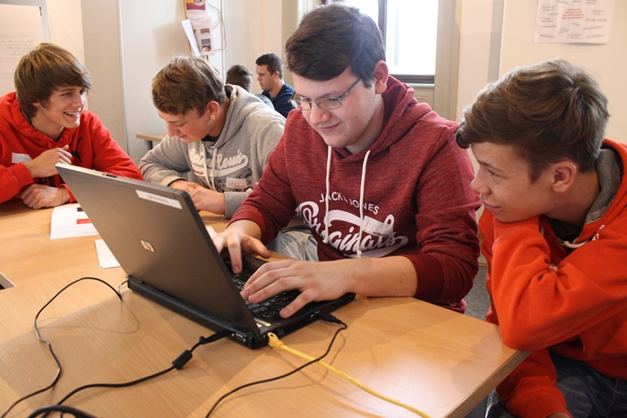 Junge Männer arbeiten gemeinsam an einem Artikel am Laptop