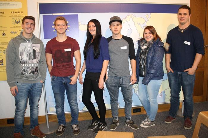 Sechs Lehrlinge posieren vor einer Europakarte