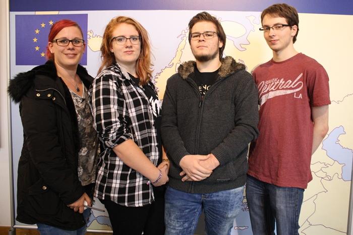 Vier Lehrlinge posieren vor einer Europakarte