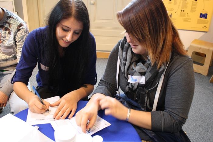 Zwei junge Frauen schreiben gemeinsam Vorschläge nieder