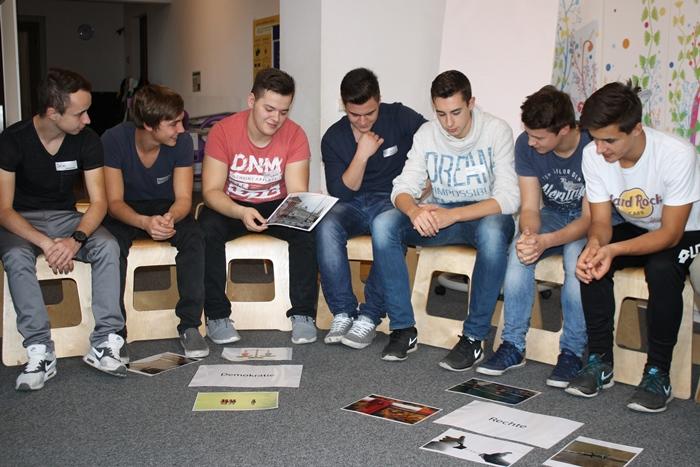 Lehrlinge im Sesselkreis diskutieren über Bilder passend zum Begriff Demokratie