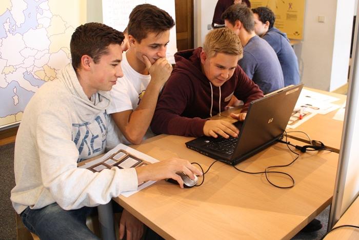 Drei Lehrlinge arbeiten gemeinsam am Laptop