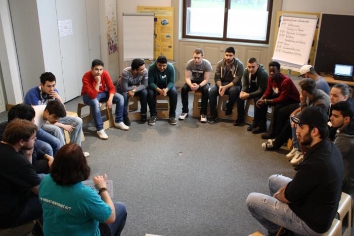 Gruppe von Lehrlingen sitzt im Sesselkreis