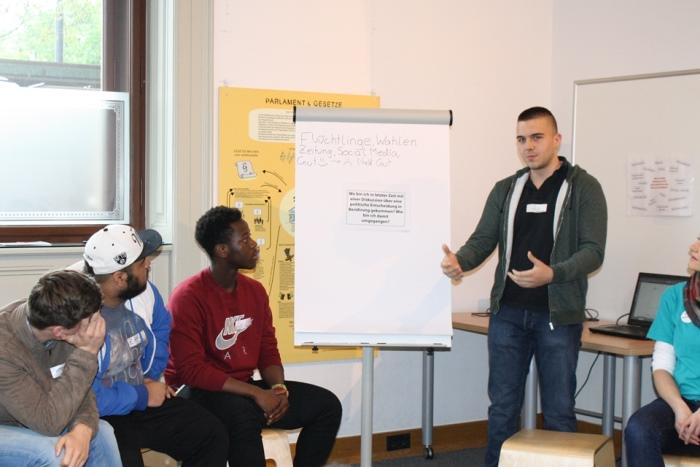 Ein Lehrling präsentiert vor einem Flipchart die Kleingruppenergebnisse