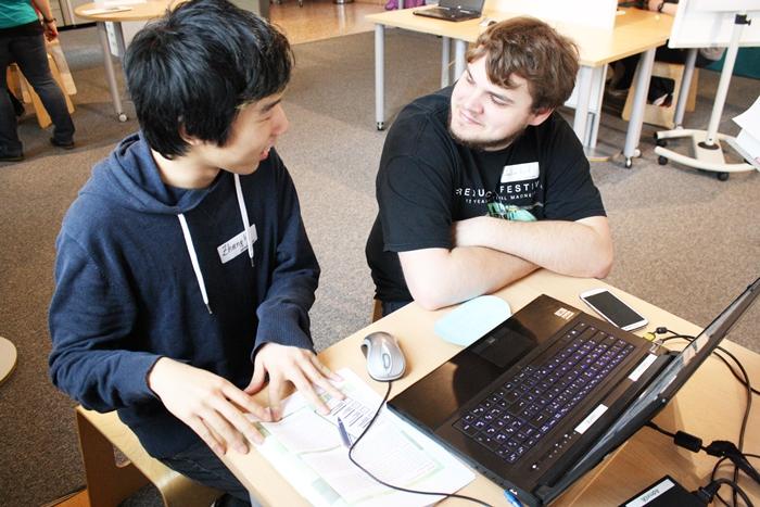 Zwei Lehrlinge vor einem Laptop während der Recherche