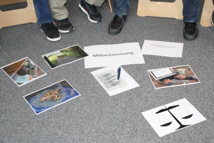 """Am Boden aufgelegte Zettel zum Begriff """"Mitbestimmung"""" und dazu passende Bilder"""