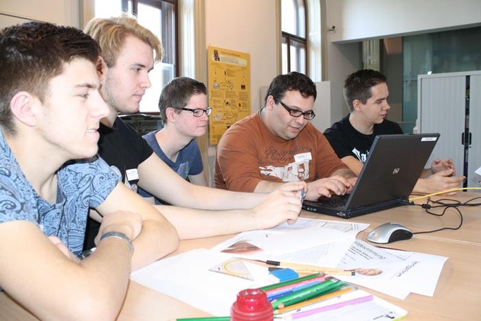 Fünf Lehrlinge verfassen gemeinsam einen Artikel am Laptop