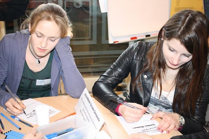 Zwei junge Frauen der Lehrlingsgruppe schreiben Ideen auf