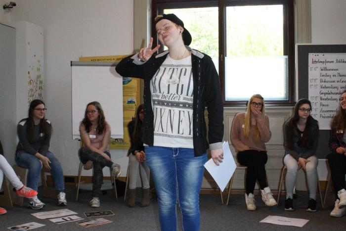 """Junge Frau der Lehrlingsgruppe steht im Sesselkreis und deutet das """"Victory Zeichen"""""""