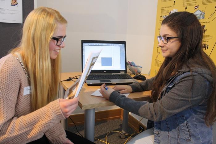 Zwei junge Frauen der Lehrlingsgruppe recherchieren gemeinsam