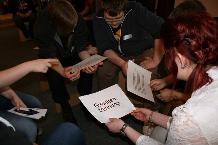 Kleingruppe von Lehrlingen diskutiert über Gewaltentrennung