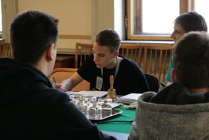 Ein Lehrling übernimmt die Rolle des Ausschussvorsitzenden und macht sich Notizen