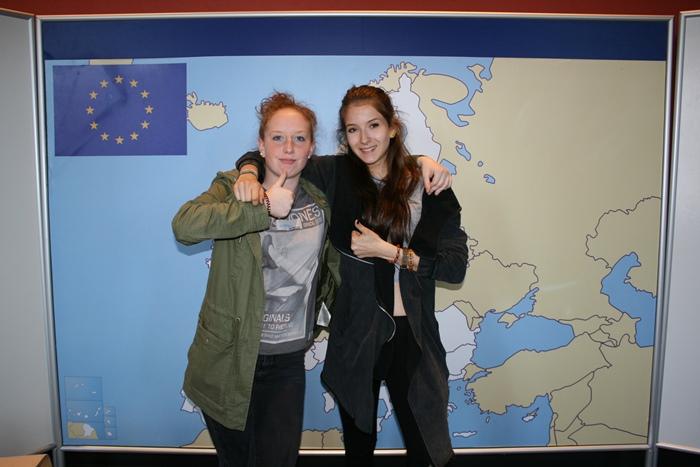 Zwei junge Frauen der Lehrlingsgruppe posieren vor einer Europakarte
