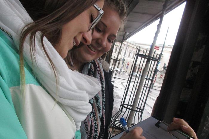 Zwei Lehrlinge führen auf der Straße eine Umfrage durch und machen Notizen