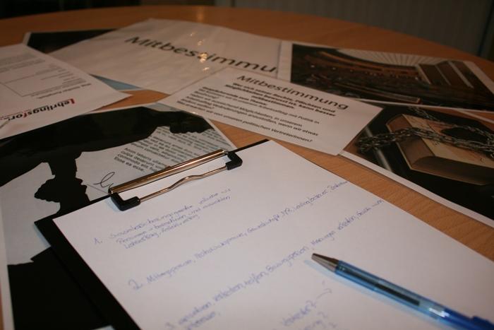 """Arbeitsmaterialien zum Thema """"Mitbestimmung"""" liegen auf einem Tisch"""