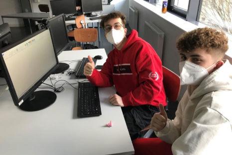 Zwei Lehrlinge sitzen vor einem Laptop und machen die Daumen hoch Geste