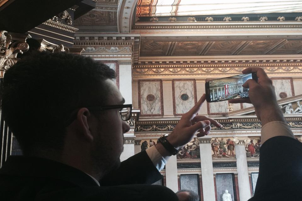 Ein Lehrling fotografiert mit dem Handy in den Historischen Sitzungssaal des Parlaments
