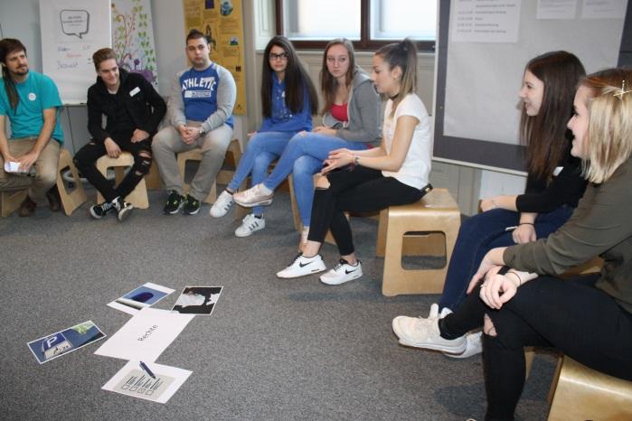 Lehrlinge sitzen auf Hockern und diskutieren