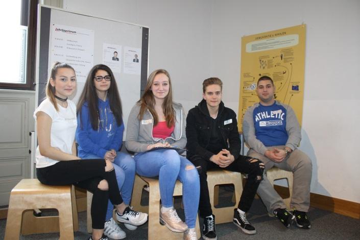 Lehrlinge sitzen vor Flipchart und Plakat