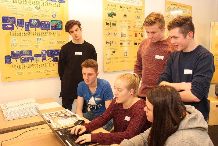 Lehrlinge sitzen auf Hockern und arbeiten am Laptop