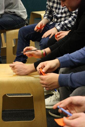 Lehrlinge sitzen auf Hocker und schreiben Zettel